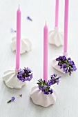 Candles in meringue candleholders decorated with lavender flowers