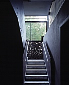 Narrow staircase with metal treads and balustrades and gabion wall