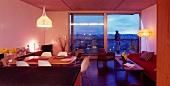 Offener moderner Wohnraum mit Essplatz und raumhohen Terrassenfenstern mit Abendstimmung
