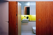 View through open door into small designer bathroom with sink and yellow painted back wall