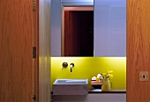 View through open wooden door into designer bathroom with sink and yellow painted back wall with indirect lighting