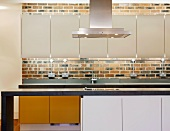 Modern kitchen units with white wall-mounted cupboards and indirect lighting on a brick wall