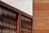 Screen fencing with woven panels and wooden frame in front of white-washed brick wall