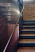 Wood and metal stairway with transparent wire mesh wall in a factory