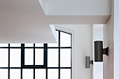 Detail of suspended ceiling in front of window with black glazing bars and modern wall lamps