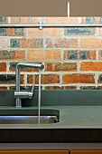 Designer tap fitting with water running into stainless steel sink in front of brick wall