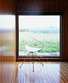 Retro chair with transparent plastic seat in front of window with a view in wood-clad modern room