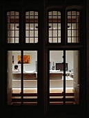 View through illuminated terrace doors with transom windows to man seated in living room