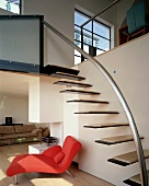 Floating stair treads on wall of living space with red chaise longue
