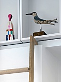 Bird figurine and modern painted figurine on white cubist shelving