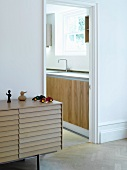Modern sideboard with overlapping slatted front next to an open kitchen door
