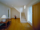 Generous foyer with table lamp on sideboard and white painted wooden stairs