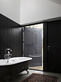 Vintage bathroom with partial black wood cladding and ceiling-height window with half-closed shutter