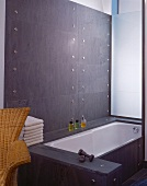 Designer cladding in grey stone on walls and bathtub with stainless steel bolts