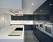 Cool designer kitchen with white kitchen units in front of black, high-gloss fitted cupboards