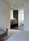 Minimalistische Ankleide mit breitem Durchgang und Blick in designtes Bad