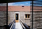 Access bridge to front door of house with facade clad in wooden slats