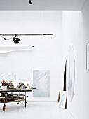 Künstleratelier mit Malutensilien auf Rollwagen und Bildern an Wand