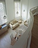 View from curved gallery onto open-plan living room with light modern sofa and upholstered furniture on a wooden floor