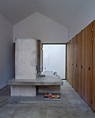 Designer bathroom with concrete partition and shelf in front of bathtub
