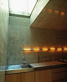 Corner of contemporary kitchen with fluorescent tubes on concrete block wall