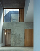 Empty foyer with large transom window and open doorway in concrete block wall