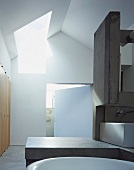Modern bathroom with skylight, concrete partition and surface in contemporary building