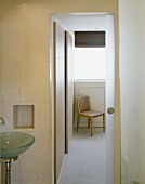 Modern bathroom with open sliding door and view of chair