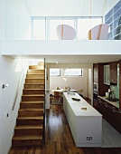 Open-plan living with kitchen area and stairs to gallery