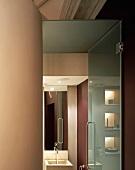 Open glass door with view into elegant modern bathroom
