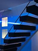 Zeitgenössische Treppe mit auskragenden Holzstufen im Dämmerlicht