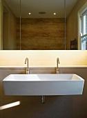 Grosses Waschbecken mit zwei Designerarmaturen unter Spiegelschrank mit indirekter Beleuchtung