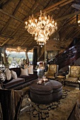 A Rococo-style furnished living room with gilded chandeliers in an African hut