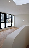 Empty living room with recessed downlights and large window in a contemporary building