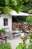 Mit Sonnensegel überdachter Sitzplatz am Haus mit Betontisch vor hoch aufgestapeltem Brennholz