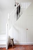 Stauraum im Einbauschrank unter weisser schlichter Landhaustreppe mit hinabgehender Person und Schemel auf Terracottaboden