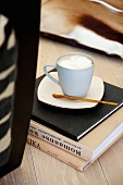 Capuccino Pause - Tasse auf Bücherstapel am Boden