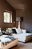 Elegantes weisses Tagesbett am Fenster in dunkelbraun getöntem Dachzimmer