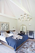 Double bed below chandelier with metal lampshades and patchwork fur rug