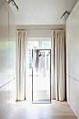 Ankleide mit weissen Einbauschränken und Metallgestell mit Kleidung auf Bügel vor Fenstertür