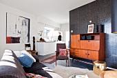 Gemütlicher Wohnraum eines Appartments mit Vintage-Möbeln aus den Fifties zu schokofarbener Wand und schlicht weisser Küchenzeile im Hintergrund