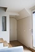 Raumecke mit eingebauten Schränken und Treppenaufgang in moderner Maisonette-Wohnung im skandinavischen Stil