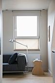 Ausschnitt einer Sitzecke im skandinavischen Designerstil mit Beistellhocker und Tolomeo Stehlampe vor Fenster mit Stoffrollo