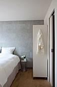 Schlafzimmer im skandinavischen Designerstil mit subtil changierender, grauer Wandgestaltung, Roll-Regal und Schiebetür zum Bad Ensuite