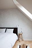 Schlafzimmer unterm Dach mit Doppelbett im Schwarzweiss-Look vor grau getönter Wand im Kontrast zu den warmen Holzfarben von Nachttischhocker und Dielenboden