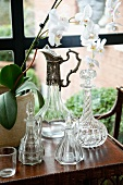 Various crystal carafes on side table