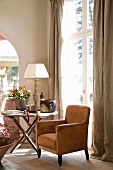 Comfortable seating area with leather armchair and side table next to French windows with floor-length curtains