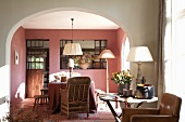View through wide arched doorway of dining table, wicker chairs and walls painted dusky pink