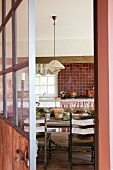 View through open door into rustic kitchen with dining area and dusky pink accents