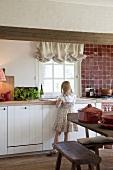 Mädchen vor Küchenzeile stehend in rustikaler Landhausküche
